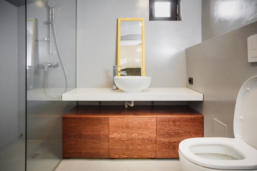 contemporary_bathroom_grey_tiles_wooden_cabinets_yellow_mirror