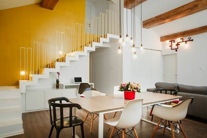 yellow_wall_white_stairs_eames_dining_chairs_open_space