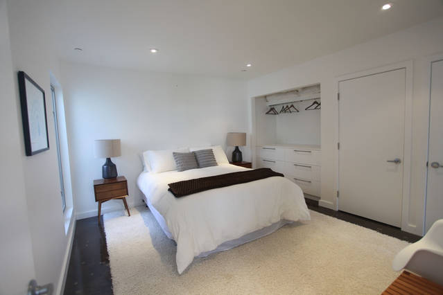 white_contemporary_bedroom_wood_nightstand_built_in_closet